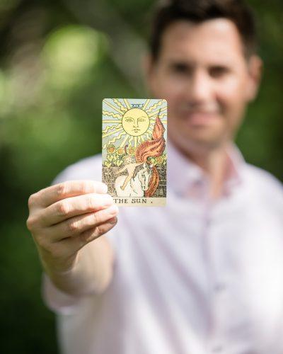 Frank holding tarot card